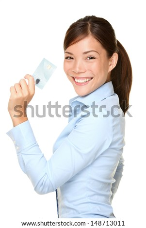 Casual business woman holding showing credit card smiling happy in blue shirt. Young female professional showing empty blank credit card sign smiling happy at camera. Beautiful Asian Caucasian model. - stock photo