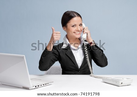 Casual business woman in office working with white table, laptop and talking by phone. Thumbs up!