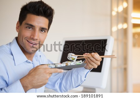 Casual businessman enjoying sushi at his desk in his office - stock photo