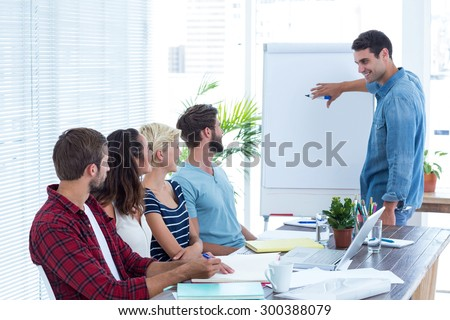 Casual businessman giving a presentation to his colleagues - stock photo