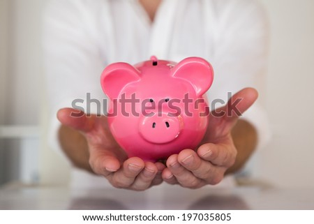 Casual businessman holding piggy bank in his office
