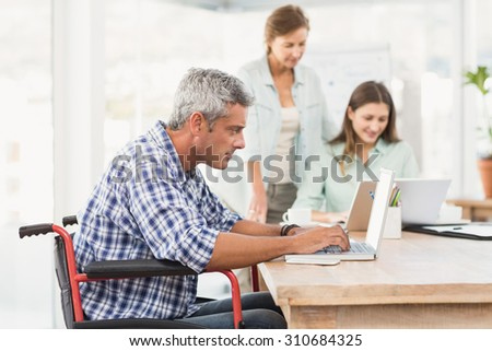 Casual businessman in wheelchair using laptop in the office - stock photo