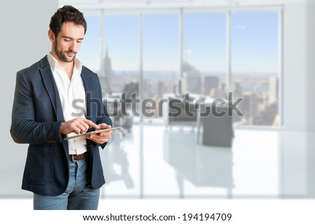 Casual Businessman Looking at a tablet, in an office - stock photo