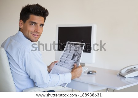 Casual businessman reading newspaper at his desk in his office