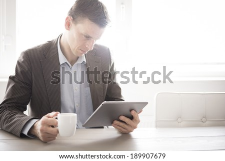 Casual businessman reading on tablet pc at the office - stock photo