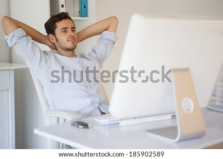 Casual businessman relaxing at desk leaning back in his office - stock photo