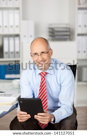 Casual businessman sitting and holding tablet computer in the office - stock photo
