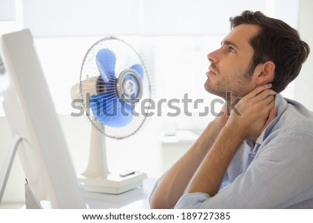 Casual businessman sitting at desk with electric fan in his office - stock photo