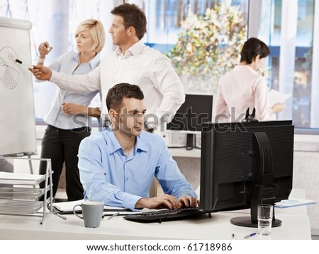 Casual businessman sitting at office desk, working on computer. Businesspeople working in background.?