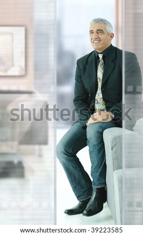 Casual businessman sitting on couch in modern office, smiling. - stock photo
