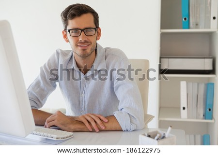 Casual businessman smiling at camera at his desk in his office - stock photo