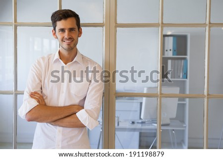 Casual businessman smiling at camera in the office - stock photo