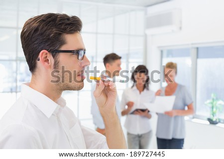 Casual businessman smoking an electronic cigarette in the office - stock photo