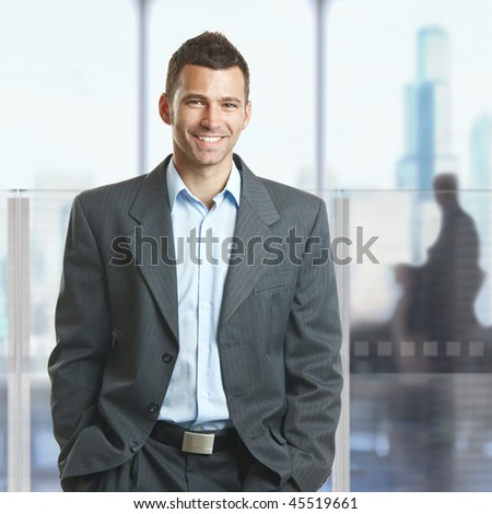 Casual businessman standing with hands in pocket in corporate office lobby, smiling. - stock photo