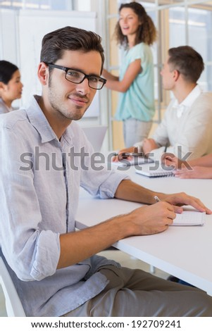 Casual businessman taking notes during meeting in the office - stock photo