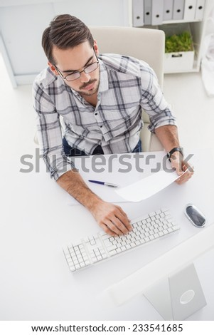 Casual businessman using his computer in his office - stock photo