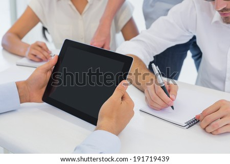 Casual businessman using his tablet during meeting in the office - stock photo