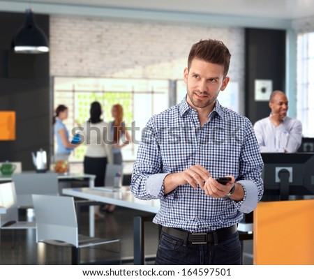 Casual businessman using mobile phone at modern stylish office, smiling. - stock photo