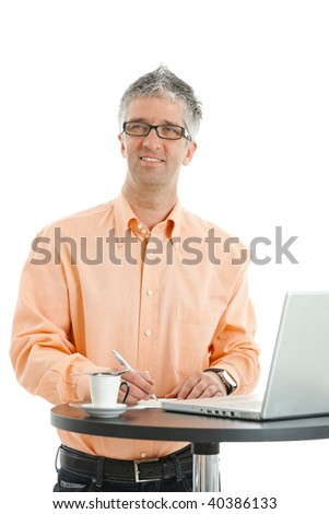 Casual businessman wearing orange shirt and jeans, writing notes at coffee table. Isolated on white.