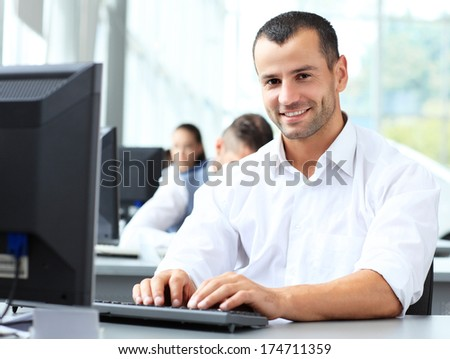 Casual businessman working in office, sitting at desk, typing on keyboard