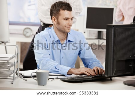 Casual businessman working in office, sitting at desk, typing on keyboard, looking at computer screen.? - stock photo