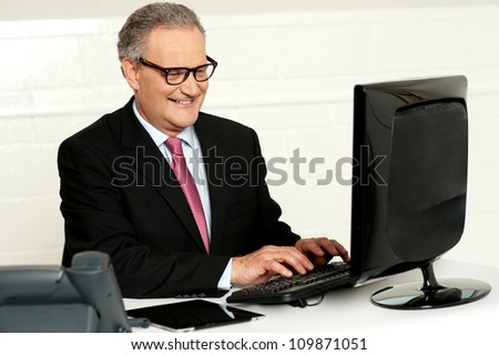 Casual businessman working in office sitting at desk typing on keyboard looking at computer screen - stock photo