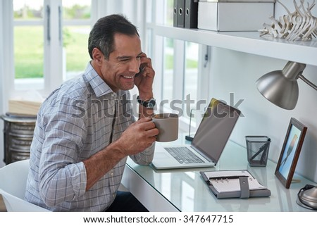 Casual businessman working remotely from home office drinking coffee and talking on mobile phone.