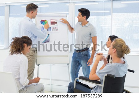 Casual businessmen giving presentation to colleagues in the office - stock photo