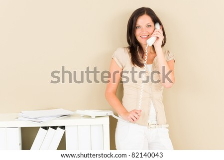 Casual businesswoman attractive smiling calling standing by bookshelf - stock photo