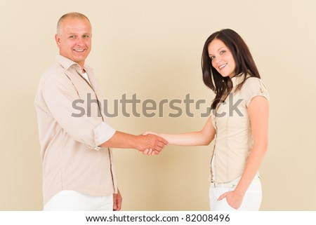 Casual businesswoman attractive smiling handshake with businessman colleague - stock photo