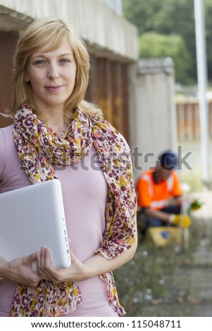 Casual businesswoman carrying laptop with construction worker in the background - stock photo
