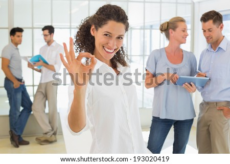 Casual businesswoman giving ok sign to camera in the office - stock photo
