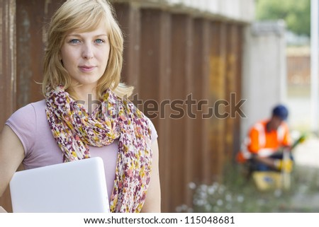 Casual businesswoman holding laptop with construction worker in the background - stock photo