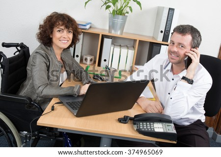 Casual businesswoman in wheelchair on the phone in office - stock photo