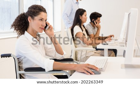 Casual businesswoman in wheelchair on the phone in the office - stock photo