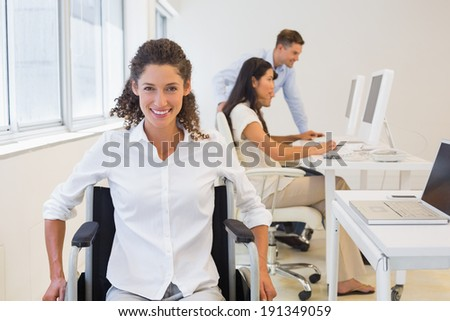 Casual businesswoman in wheelchair smiling at camera in the office