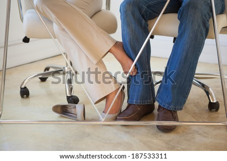 Footsie Under Table : businesspeople playing footsie under table