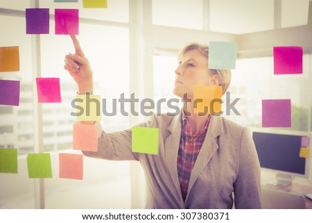 Casual businesswoman reading sticky notes in the office - stock photo