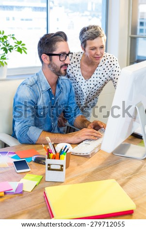 Casual businesswoman showing the screen to her partner in the office - stock photo