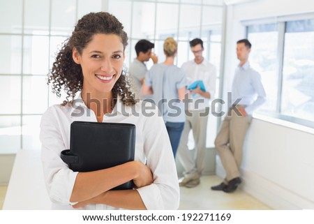 Casual businesswoman smiling at camera holding diary in the office - stock photo