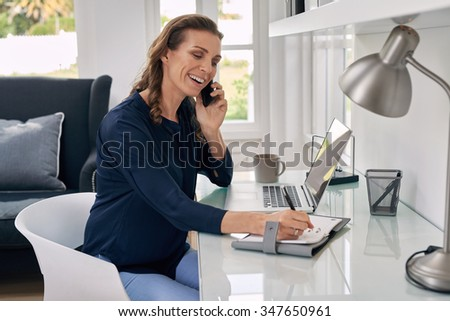 Casual businesswoman working remotely from home office writing on notepad and talking on mobile phone. - stock photo
