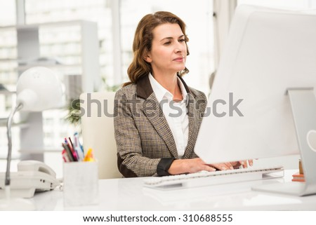 Casual businesswoman working with computer in the office - stock photo
