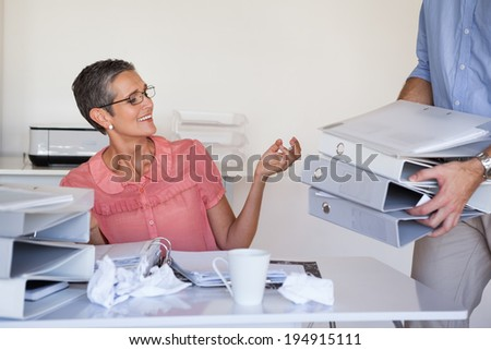 Casual businesswomans workload getting bigger and bigger in the office - stock photo