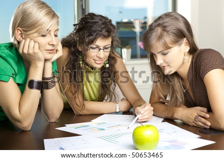 Casual businesswomen leaning on table in meeting room, discussing finacial charts. - stock photo