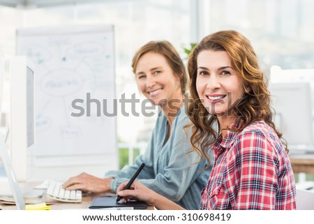 Casual businesswomen looking at computer in an office - stock photo