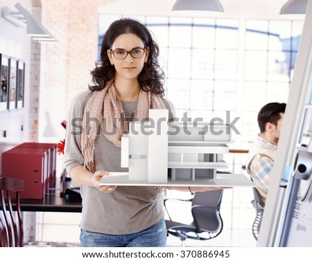 Casual caucasian attractive female architect with scale model of a building plan, standing, holding, wearing glasses, looking at camera, smiling at office. - stock photo