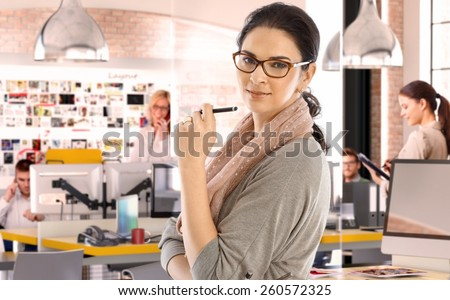 Casual caucasian businesswoman at business startup office with pen in hand, wearing glasses. Looking at camera, scarf around neck. - stock photo