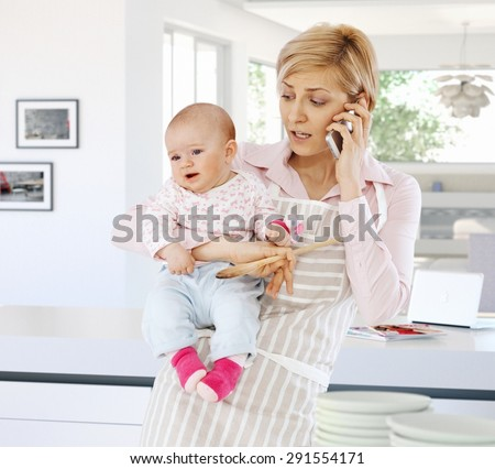 Casual caucasian housewife in kitchen with baby, phone, spoon in hand. Standing, talking on phone. Worried, stressed, busy. - stock photo