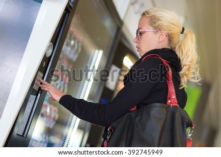 Casual caucasian woman using a modern beverage vending machine. Her hand is placed on the dial pad and she is looking on the small display screen. - stock photo