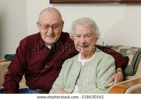 Casual close-up portrait of a happy elderly couple in their eighties sitting on a sofa in their living room. - stock photo